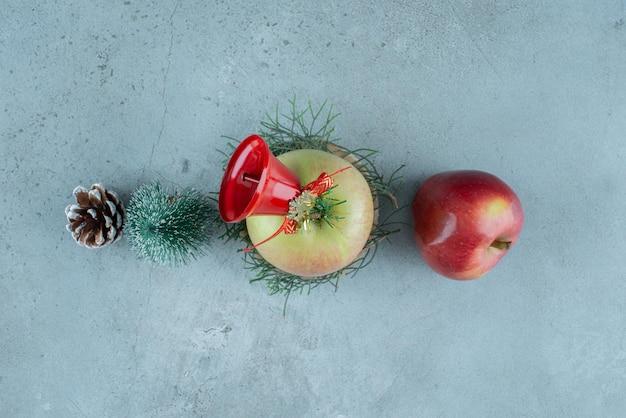 Яблоки и праздничные елочные игрушки на мраморе.