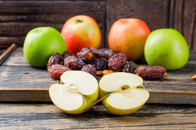Яблоки и половинки с финиками и миндалем на деревянной доске, вид сбоку на каменную плитку и деревянные