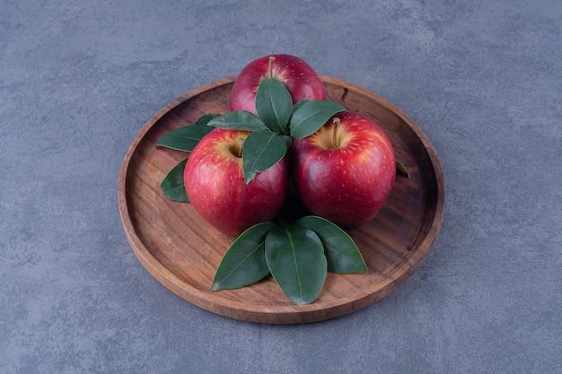 Яблоки и листья на доске на мраморном столе.