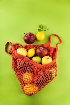 オレンジ色のひも袋に入れたリンゴとレモン