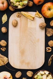 Apples and nuts around cutting board