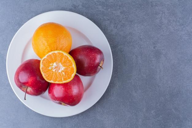 Яблоки и апельсин на тарелке на мраморном столе.