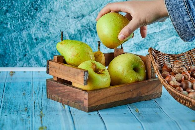 Яблоки и груши в деревянной корзине и шаре с фундуками на синей поверхности.