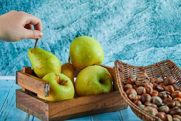 Яблоки и груши в деревянной корзине и шаре фундуков на синем столе.