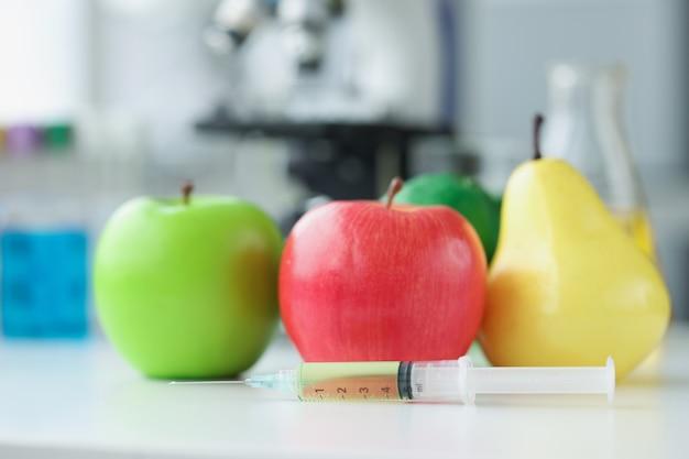Яблоки и груши, лежа на столе в лаборатории возле шприца с крупным планом медицины. концепция химического производства пестицидов