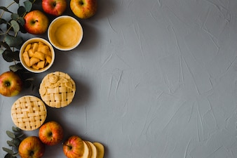 Apples and pies on plaster background