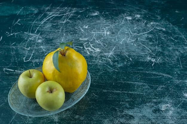 Яблоки и айва на тарелке, на мраморном столе.