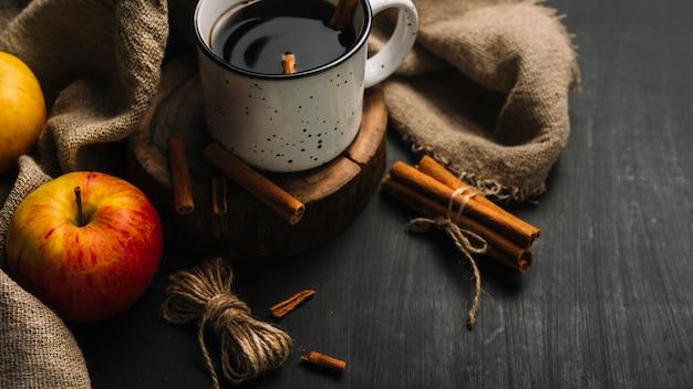 Яблоки и нитки возле ткани и пряного напитка