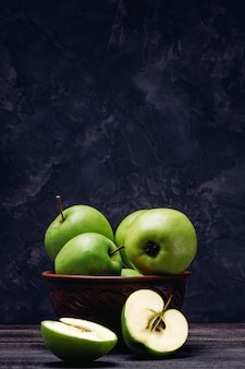 Apples are green in a bowl and a sliced apple