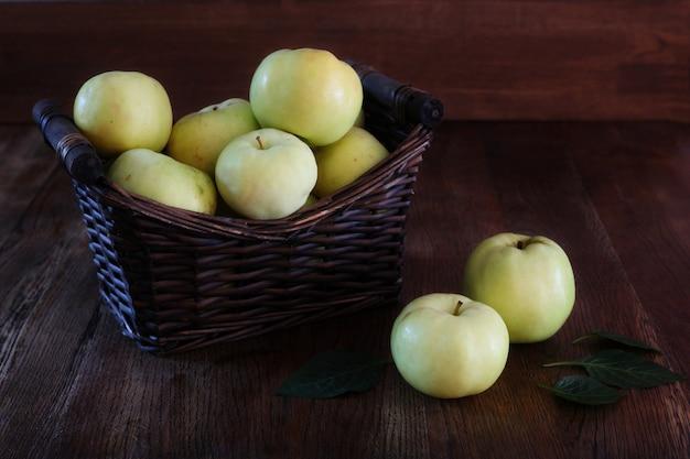 Корзина яблок. здоровое питание. деревянный фон. темное фото. передний план. скопируйте пространство.