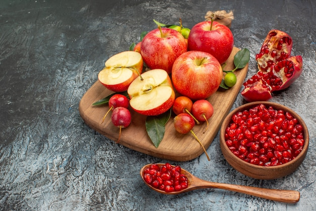 Mele ciotola di melograno mele ciliegie sul tagliere