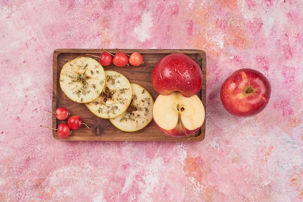 Apples and cherries on wooden board.