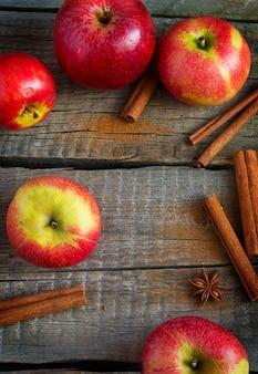 사과, 계피, 스타 아니스는 오래된 나무 배경에 있습니다.