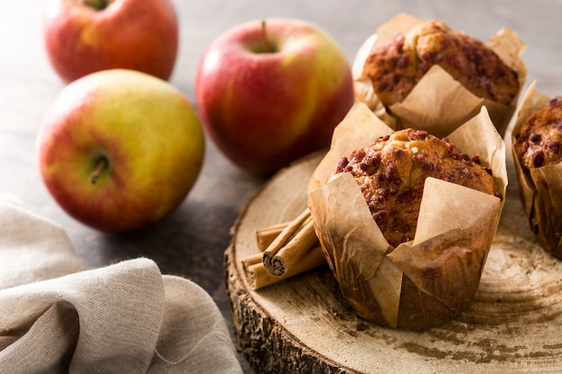 Apples and cinnamon muffins on white wooden table.