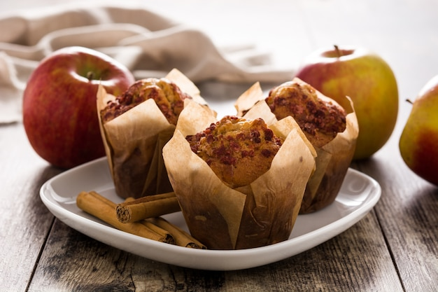 Apples and cinnamon muffins on wooden table