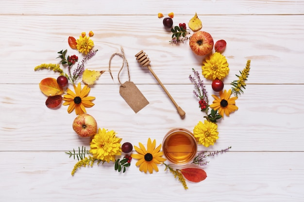 Apples, flowers and honey with copy space form a floral decoration.