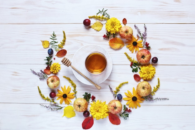 Apples, flowers and honey with copy space form a floral decoration