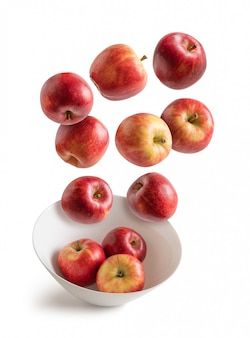 Apples flying over white bowl isolated from the background