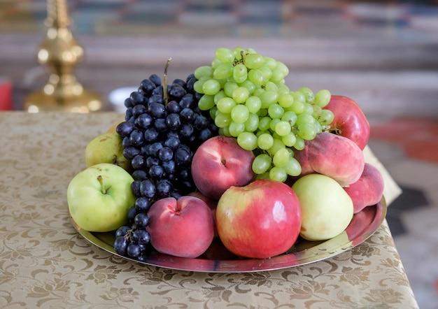 Яблоки, виноград, персики на столе в православной церкви