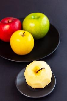 검은 벽에 껍질이없는 사과 녹색 노란색 빨간색과 사과