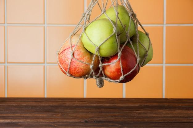 リンゴは木製とオレンジ色のタイルの背景にネットバッグにぶら下がっています。側面図。テキストのためのスペース