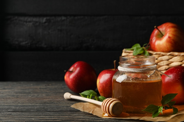Apples and honey on wood, space for text