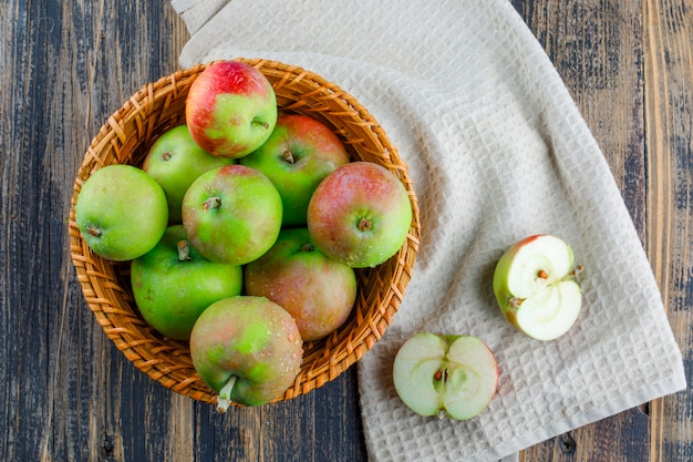 Яблоки в корзине на фоне деревянных и кухонных полотенец. плоская планировка.