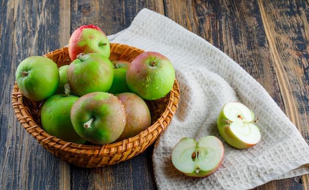 Яблоки в корзине на фоне деревянных и кухонных полотенец, высокий угол обзора.