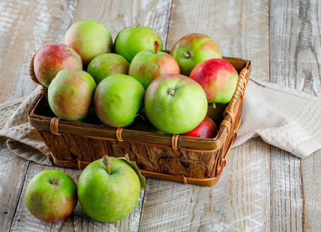 木製とキッチンタオルの上のバスケットにリンゴ。ハイアングル。
