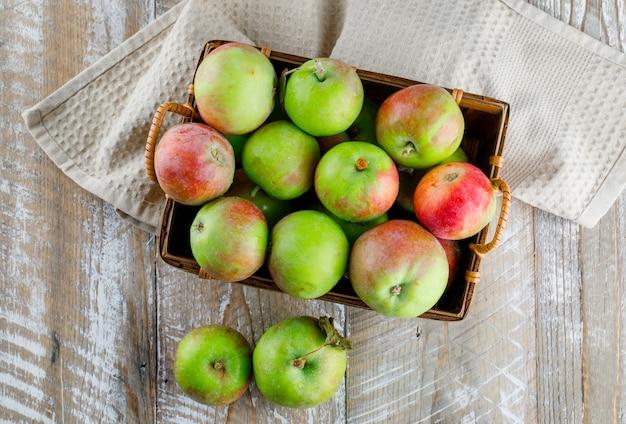 Яблоки в корзине на деревянном и кухонном полотенце