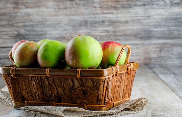 木製のバスケットとプレースマットのりんご。側面図。