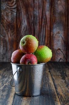 Яблоки в мини-ведре на старых деревянных фоне. вид сбоку.