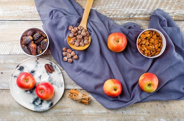 Яблоки в тарелке с палочками корицы, финиками, миндалем в мисках, орехами в деревянной ложке, вид сверху на дерево и текстиль