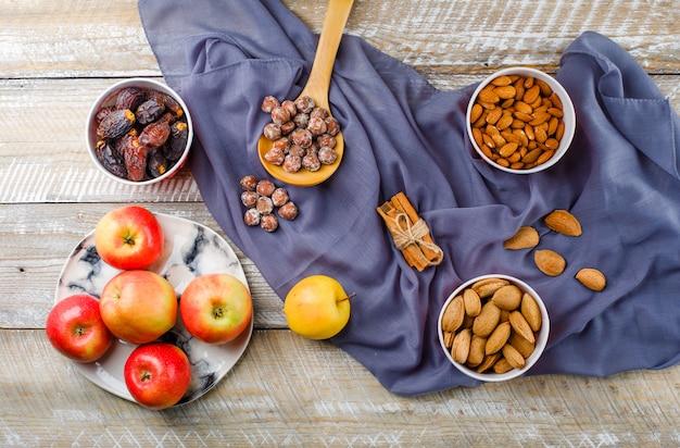 Яблоки в тарелке с палочками корицы, финиками, очищенным и неочищенным миндалем в мисках, орехами в деревянной ложке, вид сверху на дерево и текстиль