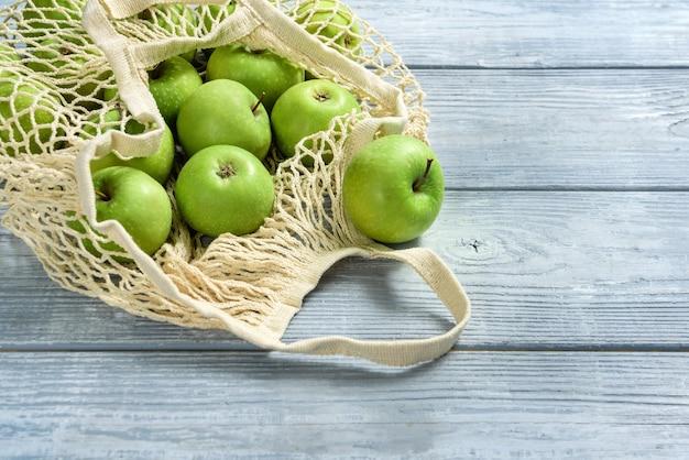 テーブルのクローズアップのストリングバッグに入ったリンゴ。コピースペースのある木の表面にリンゴが入ったショッピングバッグ。