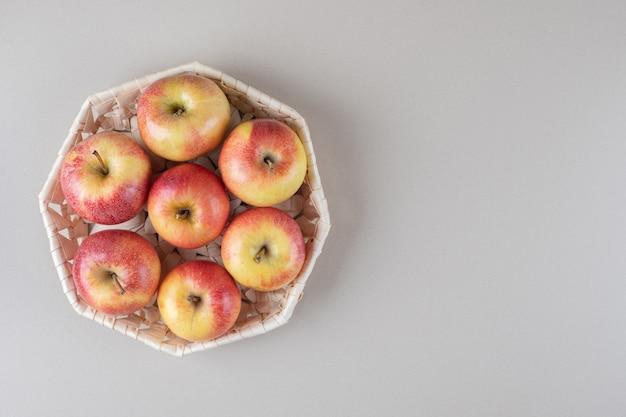 Яблоки в белой корзине на мраморе