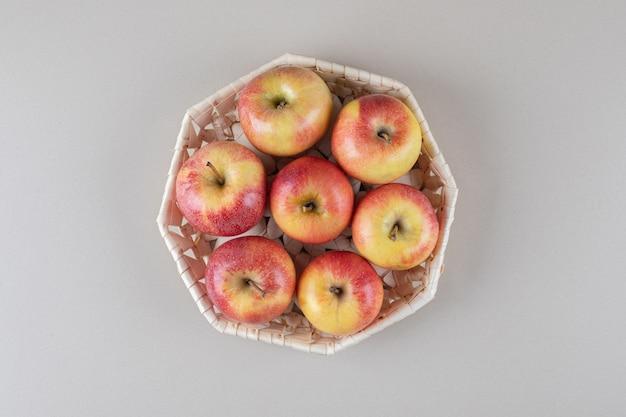 大理石の白いバスケットに入ったリンゴ