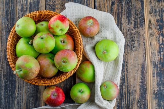 Яблоки в плетеной корзине на деревянном и кухонном полотенце. плоская планировка.
