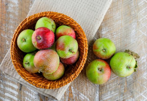 Яблоки в плетеной корзине на деревянном и кухонном полотенце ..