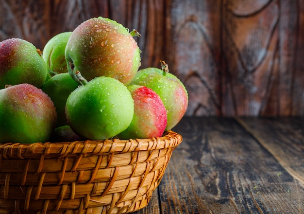 Яблоки в плетеной корзине, вид сбоку на старый деревянный фон