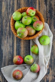Яблоки в плетеной корзине, вид сверху на деревянном и кухонном полотенце