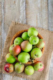 Яблоки в плетеной корзине, вид сверху на деревянный и кусок мешка
