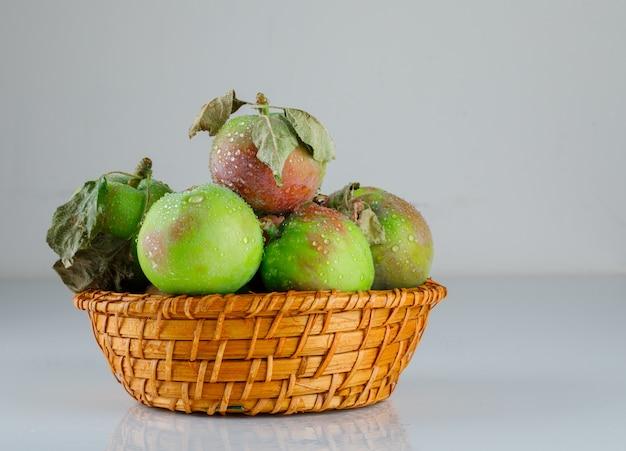 Яблоки в плетеной корзине с листьями, вид сбоку на белом градиенте