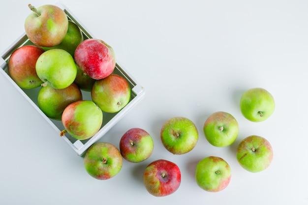 Яблоки в деревянном ящике на белом