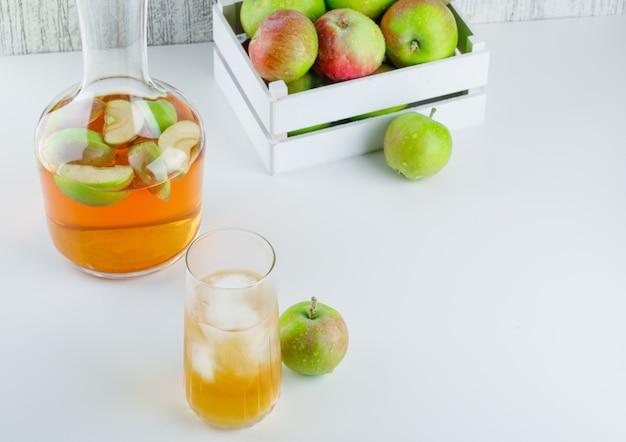Яблоки в деревянной коробке с напитком под высоким углом зрения на белом и шероховатом