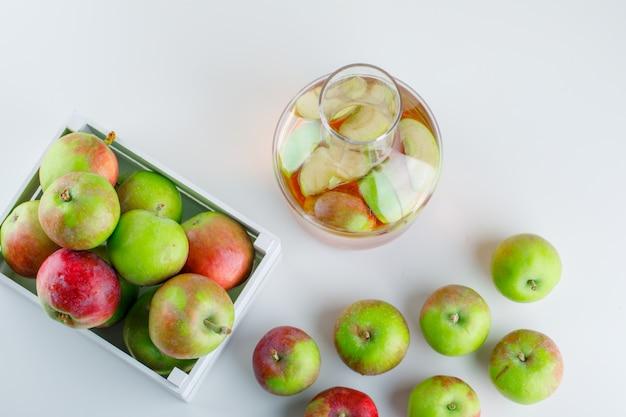 Яблоки в деревянной коробке с видом сверху сок на белом