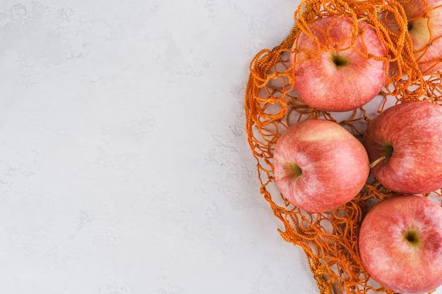 明るい灰色の背景にオレンジ色の袋にリンゴ。プラスチックではなく、天然素材と天然物のみ。