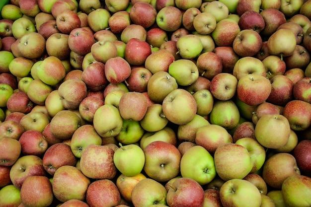 Яблоки на рынке, фон зеленые и красные яблоки