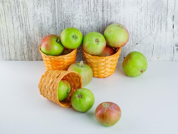 白と汚れた、高角度のビューの枝編み細工品バスケットのりんご。