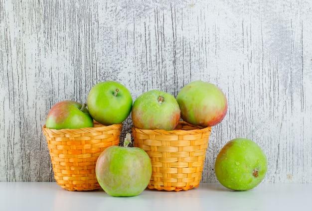 白と汚れた枝編み細工品バスケットのリンゴ。側面図。